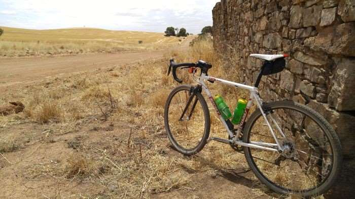 JOM's bike leaned up against the remains of a building, circa 19th century.