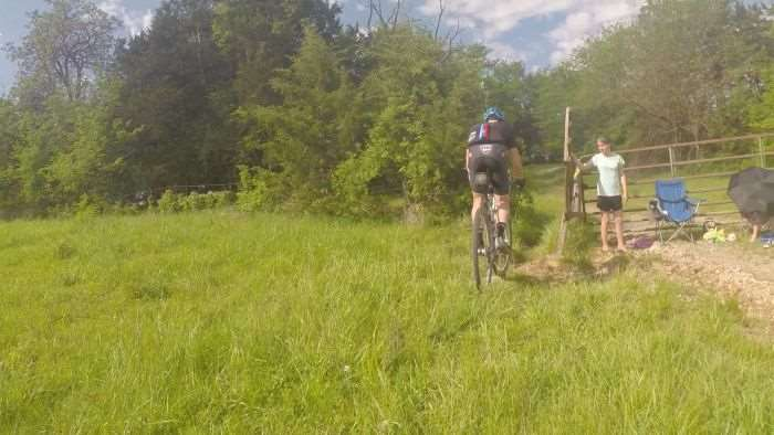 A friendly volunteer opens the gate leading to Singletrack #1.