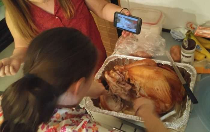 Cutting up turkey with the guidance of YouTube. Faces hidden to protect the innocent.